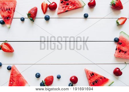 Summer Fruits. Fresh Juicy Berries And Watermelon On The White Wooden Table, Top View