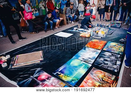 Moscow, Russia- June 12, 2017: Arbat Street. Arbat historical centre of Moscow Street art and architecture Street artist peeks for graffiti on canvas.
