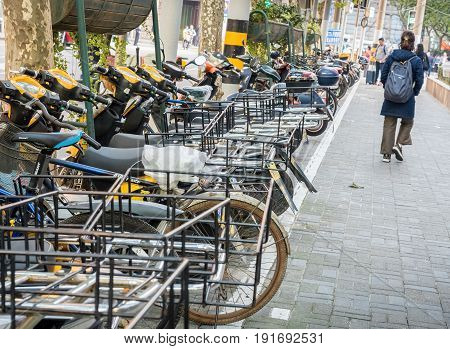 Shanghai, China - Nov 4, 2016: Along Sichuan Road (Middle) - Motorbikes and bicycles parked along the footpath shared by pedestrians. Street photography.