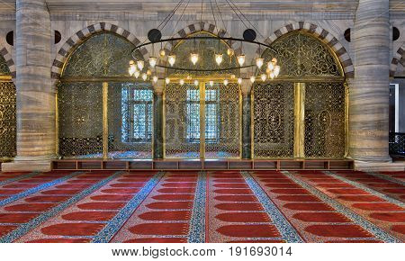 Interior shot of three arched ornate engraved golden doors big chandelier over marble wall with pillars and red decorated carpet at Suleymaniye Mosque Istanbul Turkey