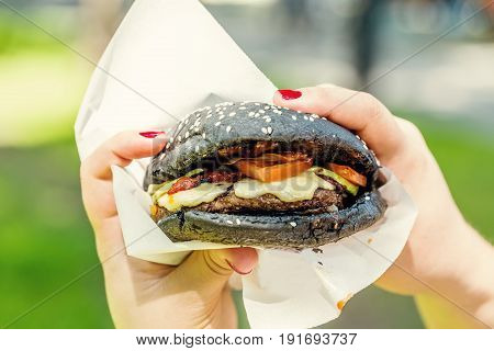 Woman hand holding tasty burger with black bread outdoors.