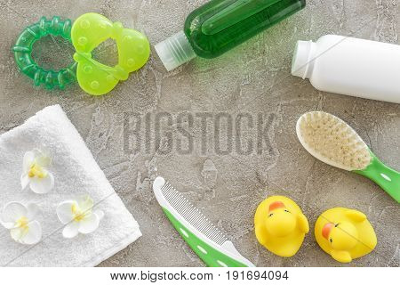 Baby care with bath cosmetic set, ducklings and towel on light gray background top view mockup