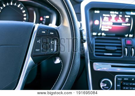 Media control buttons on the steering wheel in black leather with computer monitor modern car interior