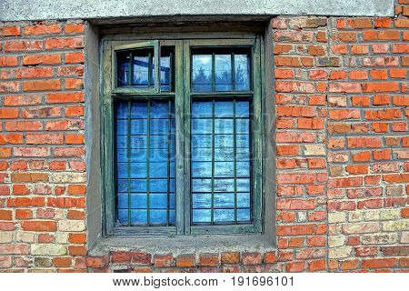 The old window with a window leaf boarded up and a lattice on a brick wall