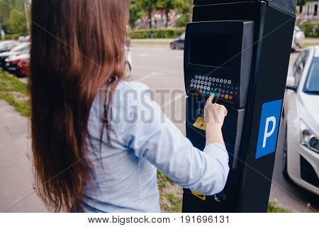 girl draws up a ticket to pay for the place of the car for parking and payment of the road. Concept of new technologies in road transport and toll roads.