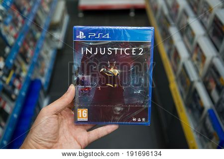 Bratislava, Slovakia, june 15, 2017: Man holding Injustice 2 videogame on Sony playstation 4 console in store