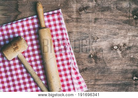 Old wooden vintage kitchen utensils on a red napkin empty space on the left