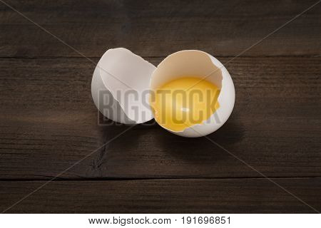 Egg smashed with yolk on a wooden background