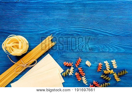 Assortment of different shape italian pastas on blue wooden table top view copyspase.