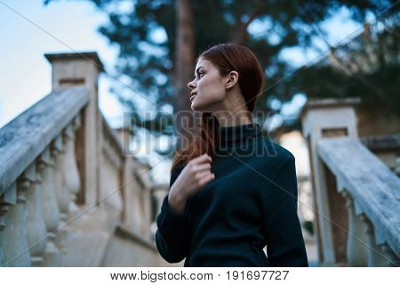 Woman staring into the background of a staircase.