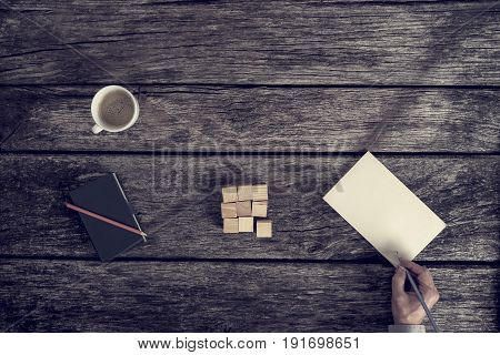 Top view of male hand making notes on a blank piece of paper lying on desk with wooden cubes in a square shape note pad and cup of coffee.