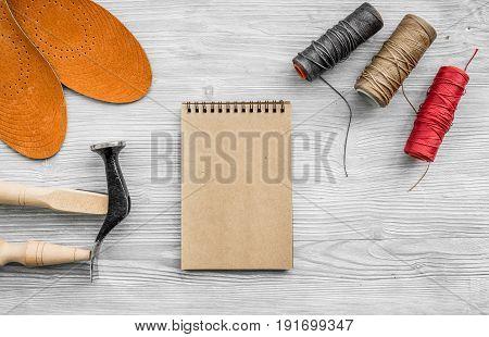Cobbler takes order. Notebok on grey wooden desk background top view mockup.