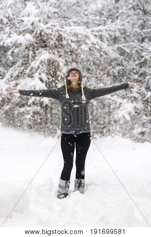 Woman standing in a snowy woodland welcoming snowflakes and celebrating life with her arms spread widely.