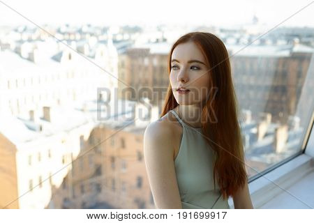 Portrait of beautiful redhead female student in cafe on the top floor and looks through the window at the city waiting her boyfriend. Attractive young woman looking away with dreamy expression