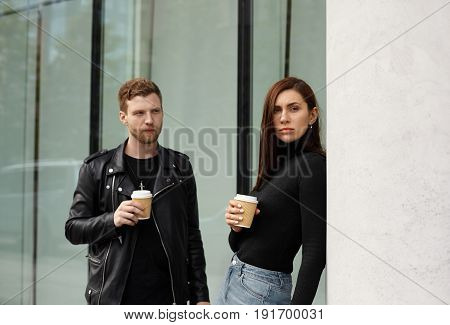 Lovers problems concept relationship conflict. Unhappy girl ignoring man not talking to boyfriend. Offended young woman turned away from her boyfriend standing near business centre in dowtown area