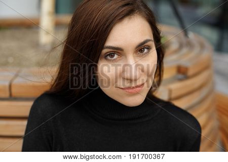 Cropped shot of young brunette woman with brown eyes and lazy smile looking at camera. Close up portrait of beautiful Chinese language translator female in black jumper sitting on the bench outdoor