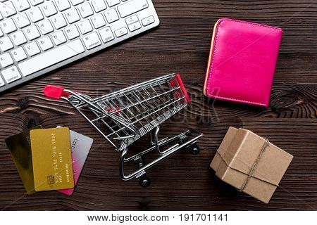 office desk with mini trolley and cards for online buying on wooden background top view