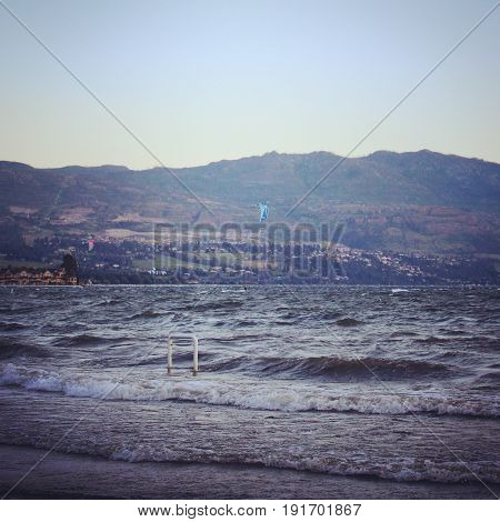 Waves rolling along lake shore on windy day with parasailing people on rough water. Buildings and mountains in background.