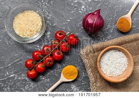 cooking paella with vegetables and rice on dark kitchen desk background top view