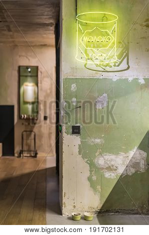 Luminous room in a loft style with shabby walls and a parquet on the floor. There is a glowing yellow signboard on the wall, mirror, switches and pet's green bowls on the floor. Vertical.