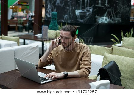 Portrait of attractive hipster in market place working laptop and start up new internet project. Skilled journalist get photo material in internet and write article news.