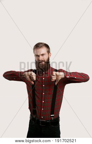 Dislike concept. Stylish beard man show unlike sign. Isolated shot of fashion hipster guy in red shirt with suspenders and dark jeans on white background. Thumb down concept.