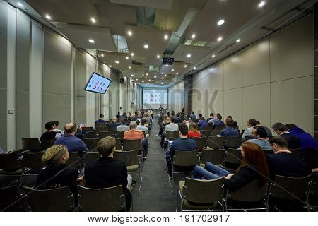 MOSCOW, RUSSIA - APR 25, 2017: People in auditorium listen to speaker during AI Conference in Novotel Moscow City Hotel. Conference is devoted to introduction of artificial intelligence in business.