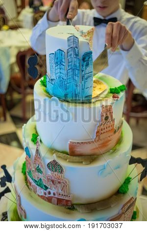 MOSCOW - APR 20, 2017: Big cake and waiter with knife at business conference Second breath of real estate market in Moscow business club in Congress-park Volynskoe