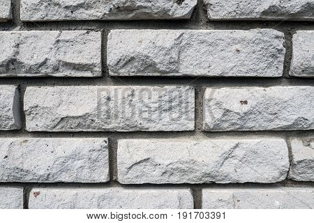 Faceted wall of white bricks with a window. Background construction of the walls of the building.