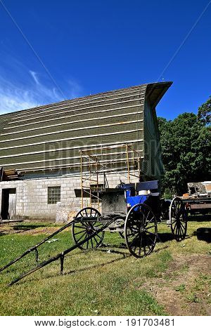 The first step in laying stringers by an unidentified Amish laborer  who traveled to the worksite in a buggy on an old barn for the covering of a metal roof
