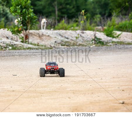 Radio controlled car model in race quickly moving on the sandy road