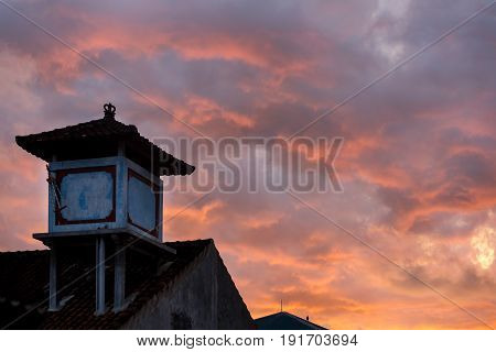 Silhouette of Asian house with a tiled roof against the sky with clouds sunset