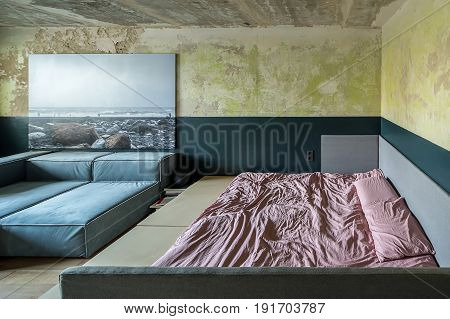 Bedroom in a loft style with shabby walls and a parquet on the floor. There are sofas, large wooden bed with rose linens and pillows, big photo on the wall, books with a speaker. Horizontal.