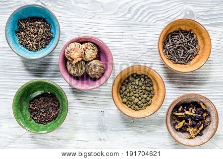 Tea-party with different herbal tea on gray wooden kitchen desk background flat lay