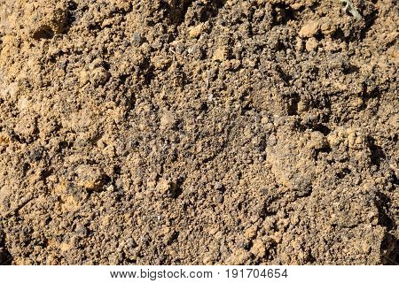 Texture is lumpy pit sand. The background of the industrial sand for construction works. Natural material for bricks and concrete products.
