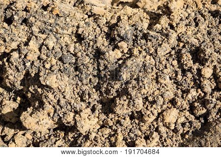 The texture is lumpy wet pit sand . The background of the industrial sand for construction works. Natural material for bricks and concrete products.