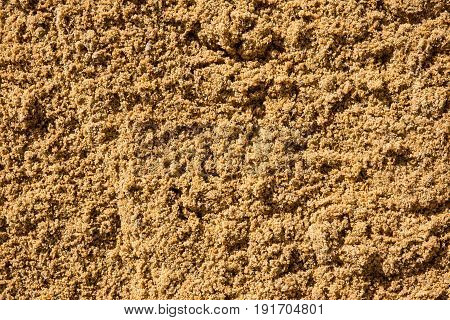 Texture of the sand. Industrial sand for construction works. Natural material for bricks and concrete products - loose rock, which contains grains of feldspar, mica, quartz and other minerals.