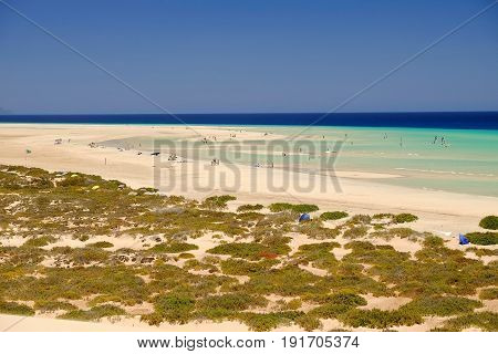 View on the beach Sotavento with golden sand and pools of ocean water with wind serfers on Costa Calma on the Canary Island Fuerteventura Spain.