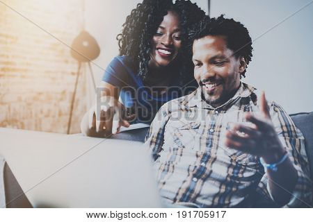 Happy african american couple relaxing together on the sofa.Young black man and girl using modern laptop for video conversation with friends.Horizontal, blurred background.Flares effect