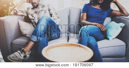 Young displeased black couple.American african men arguing with his girlfriend, who is sitting on sofa on couch next to him with legs crossed.Man looking away offended expression on her face.Cropped
