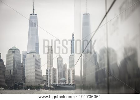USS Kearsarge (LHD 3) passes the Freedom Tower and WTC in Manhattan with reflections on the NJ 9/11 Empty Sky Memorial during the Parade of Ships, Fleet Week New York, JERSEY CITY NJ MAY 24 2017.