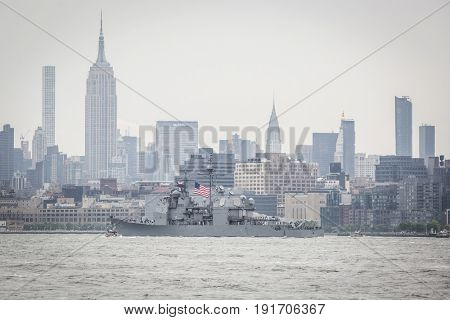 USS San Jacinto (CG 56) passes the Empire State Building in Manhattan during the Parade of Ships on the Hudson River at the start of Fleet Week New York, JERSEY CITY NJ MAY 24 2017.