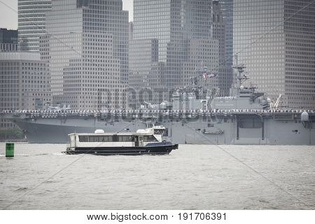NY Waterway Ferry passes USS Kearsarge (LHD 3) near Lower Manhattan WTC Financial District on the Hudson River during the Parade of Ships, the start of Fleet Week New York, JERSEY CITY NJ MAY 24 2017.