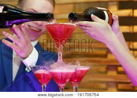 A spill of champagne glasses on a luxury party in color. A banquette with pyramid alcohol is lit with colored lights.