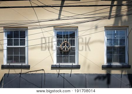 Three windows with a lot of wires and handmade PEACE SIGN hanging on the middle window.