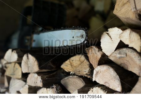 Electric saw on a stack of firewood with a blurred background