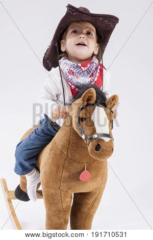 Children Consepts. Little Cheerful Caucasian Girl in Cowgirl Clothing Riding Toy Horse Against White Background.Vertical Image Composition