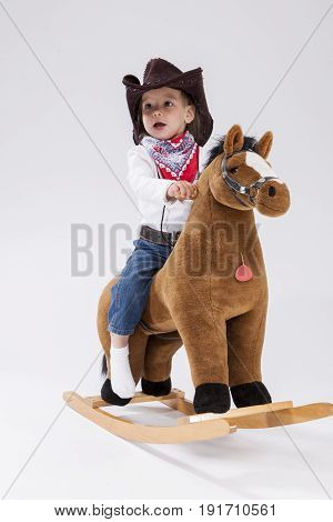 Little Children Consepts. Smiling Happy Little Caucasian Girl in Cowgirl Clothing Posing On Symbolic Horse Against White. Vertical Image Orientation
