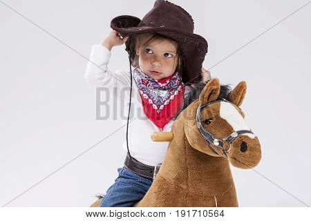 Little Children Consepts. Little Caucasian Girl in Cowgirl Clothing Posing On Symbolic Horse Against White. Holding Her Statson. Horizontal Image Orientation