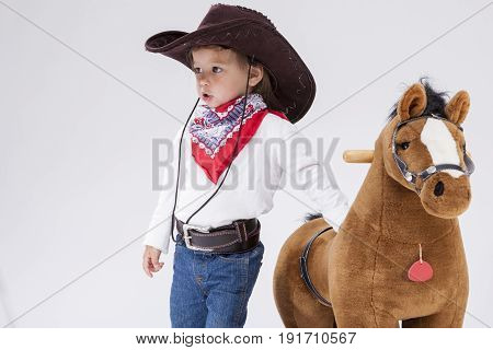 Little Children Consepts. Caucasian Girl in Cowgirl Clothing Posing With Symbolic Plush Horse Against White. Directing Forward. Horizontal Image Composition